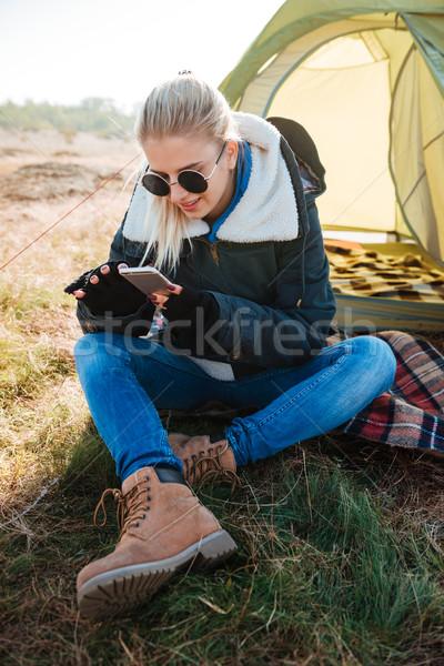 Nő napszemüveg telefon ül sátor fiatal Stock fotó © deandrobot