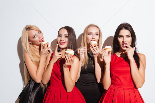 Portrait of four happy attractive young women tasting cupcakes Stock photo © deandrobot
