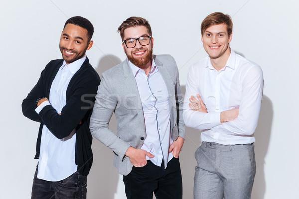 Három mosolyog fiatal férfiak áll keresztbe tett kar fehér Stock fotó © deandrobot