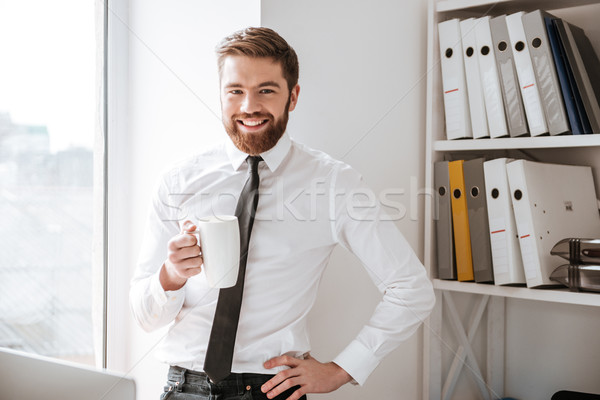 Happy young businessman looking at camera. Stock photo © deandrobot