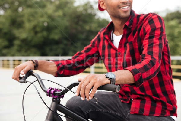 Cropped picture of happy dark skinned guy sitting on bicycle Stock photo © deandrobot