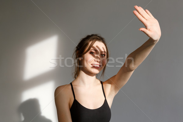Portrait of a pretty fitness woman standing with outstretched arm Stock photo © deandrobot