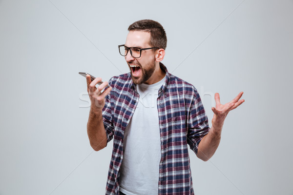 Bearded man in eyeglases screaming in phone Stock photo © deandrobot