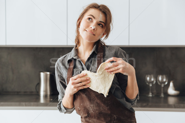 Thoughtful woman holding the dough heart. Stock photo © deandrobot