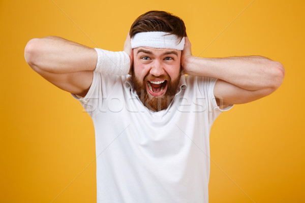 Screaming bearded sportsman covering his ears Stock photo © deandrobot