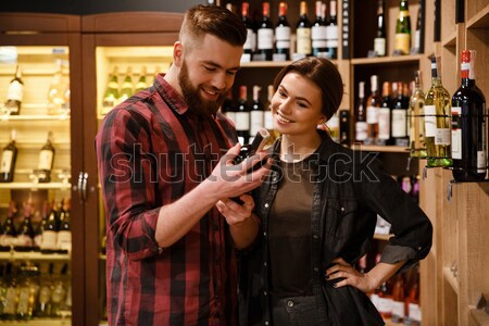 Concentrated happy loving couple in supermarket choosing alcohol Stock photo © deandrobot