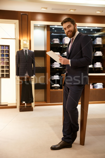 Full-length shot of man in officialwear with tablet and in wardrobe Stock photo © deandrobot