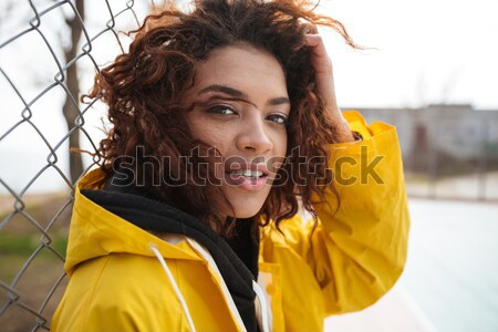 Smiling african curly young lady wearing yellow coat Stock photo © deandrobot
