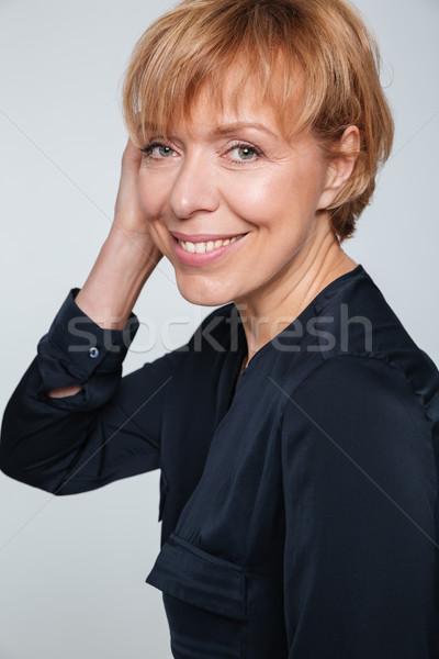 Vertical image of happy elderly woman standing sideways Stock photo © deandrobot