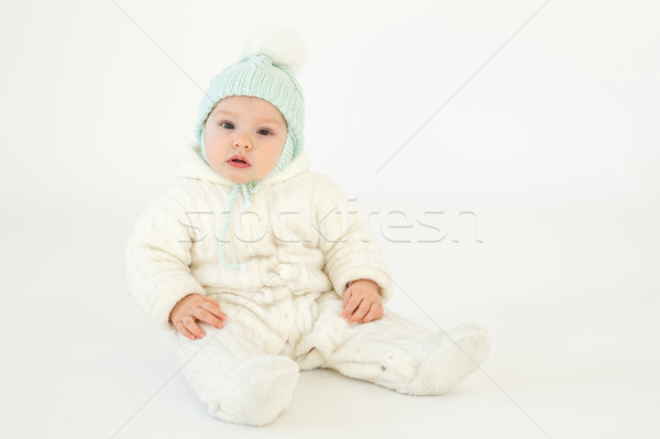 Cute little baby sitting on floor over white background Stock photo © deandrobot