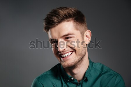 Stock photo: Happy young man posing isolated over grey background
