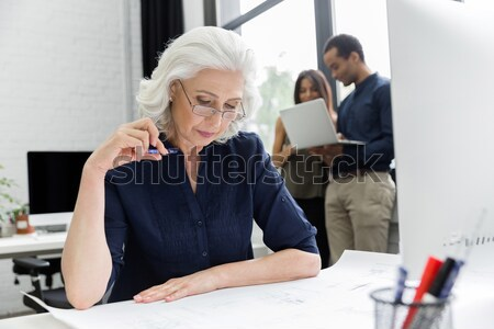 Smiling mature business woamn sitting at her workplace Stock photo © deandrobot