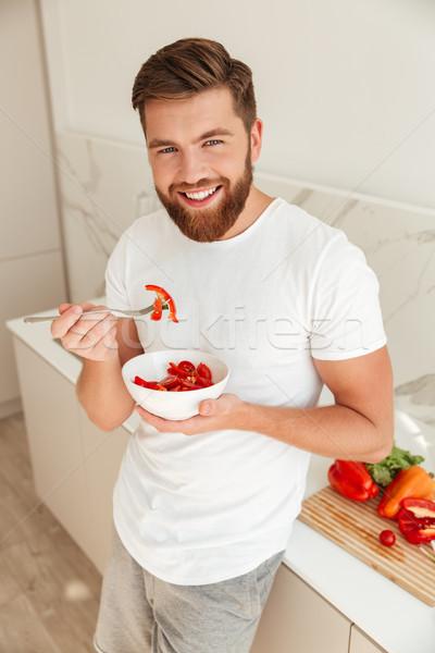 Verticale immagine sorridere barbuto uomo mangiare Foto d'archivio © deandrobot