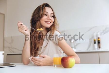 érzelmes csinos hölgy konyha eszik gyümölcssaláta Stock fotó © deandrobot
