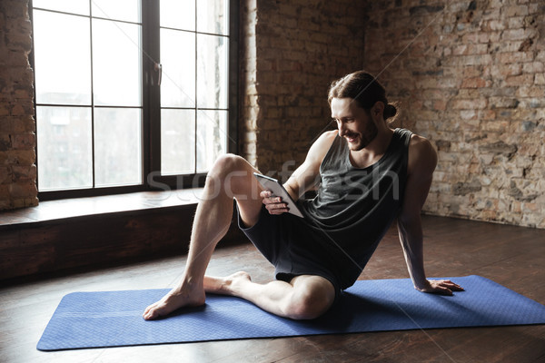 Happy strong sportsman lies on floor chatting by tablet Stock photo © deandrobot