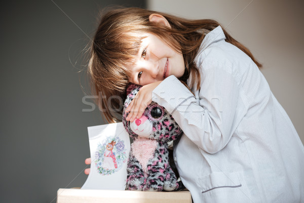 Smiling girl hugging toy and showing postcard Stock photo © deandrobot