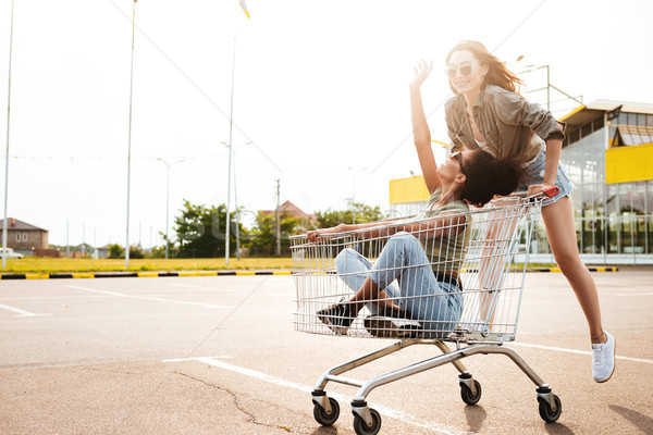 Happy women friends have fun with shopping trolleys. Stock photo © deandrobot