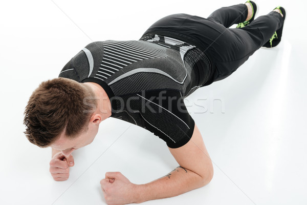 Portrait of a young fitness man doing plank exercise Stock photo © deandrobot