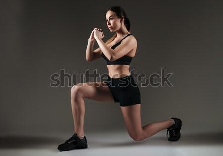Strong sportswoman make sports exercises over grey background Stock photo © deandrobot