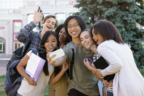 Multiethnic group of young happy students make selfie outdoors Stock photo © deandrobot