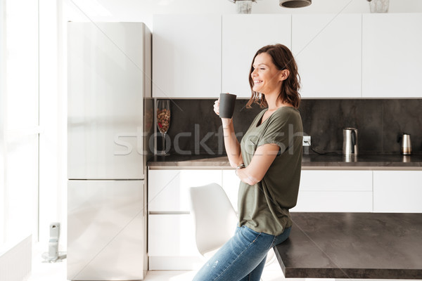 Side view of smiling casual woman drinking coffee on kitchen Stock photo © deandrobot