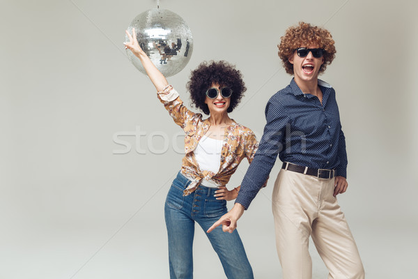 Smiling retro loving couple near disco ball. Stock photo © deandrobot
