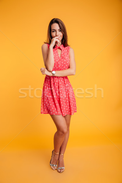 Full length photo of charming woman in red dress, looking at cam Stock photo © deandrobot