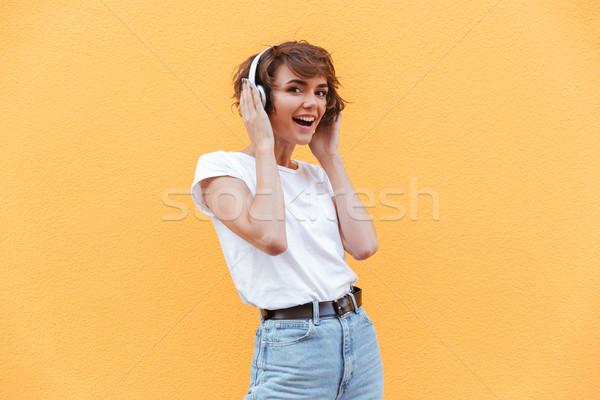 Felice ragazza denim pantaloncini ascoltare musica Foto d'archivio © deandrobot