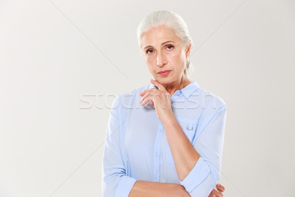 Portrait of charming serious old lady, in blue shirt, touching h Stock photo © deandrobot