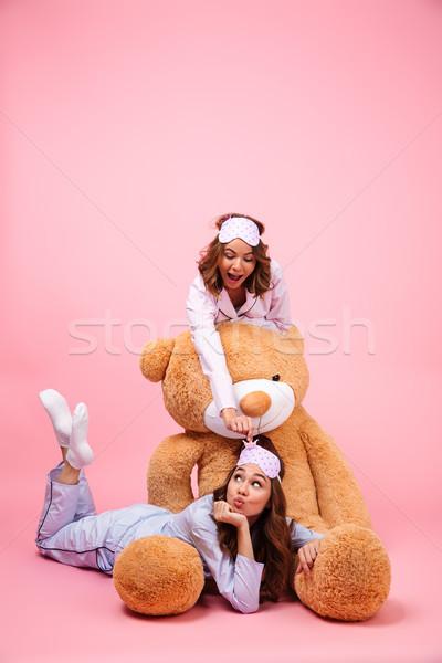Kettő derűs fiatal lányok pizsama ül Stock fotó © deandrobot