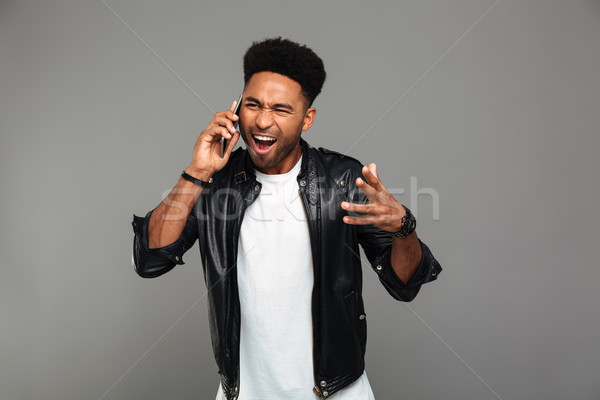Close-up photo of angry young african man screaming while talkin Stock photo © deandrobot