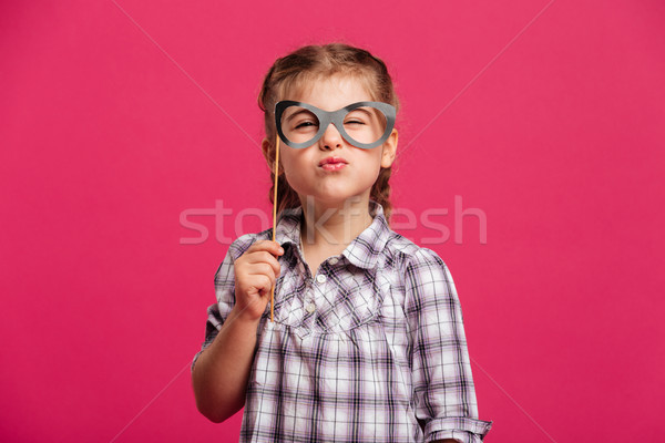 Funny little girl child holding fake glasses. Stock photo © deandrobot
