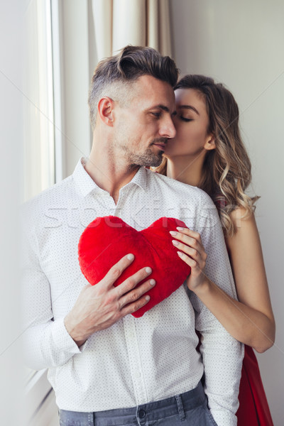 Young gorgeous lady in red dress kiss her man and holding plush toy heart Stock photo © deandrobot