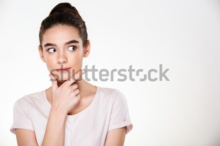 Image of serious woman with brown hair in bun touching her chin  Stock photo © deandrobot