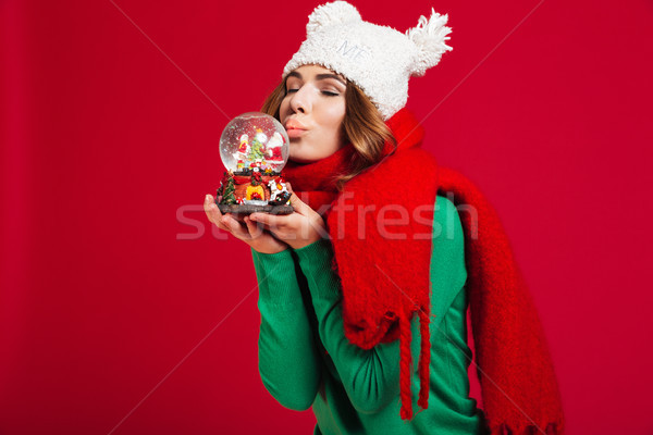 Beautiful woman holding christmas toy with eyes closed kissing. Stock photo © deandrobot