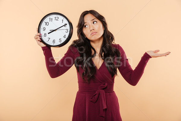 Puzzled brunette woman with curly long hair holding clock showin Stock photo © deandrobot