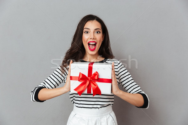 Portrait of a happy girl holding present box Stock photo © deandrobot
