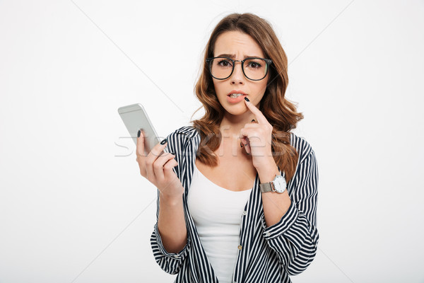 Portrait of an upset casual girl holding mobile phone Stock photo © deandrobot