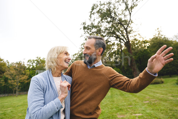 Positive happy mature couple hugging while standing together Stock photo © deandrobot