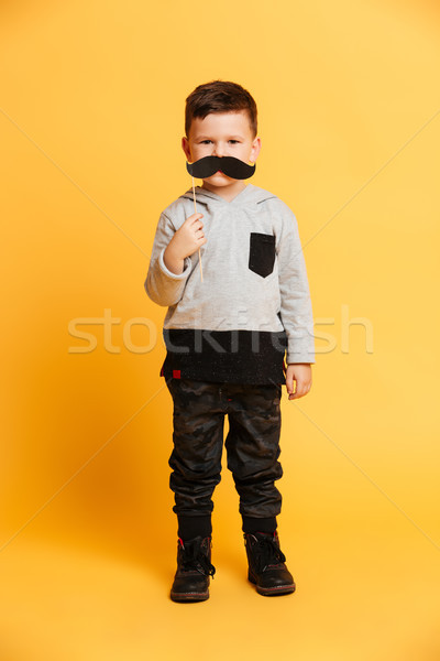 Cute little boy child holding fake moustache. Stock photo © deandrobot