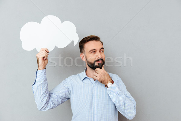 Pensive bearded man in business clothes holding blank speech cloud Stock photo © deandrobot
