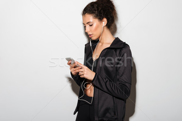 Calm curly brunette fitness woman listening music and using smartphone Stock photo © deandrobot