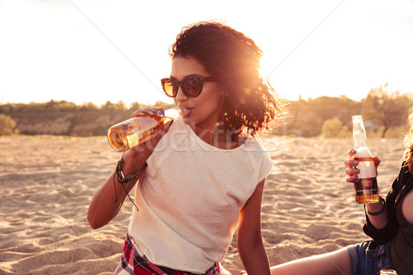 Young group of friends outdoors on the beach drinking beer. Stock photo © deandrobot