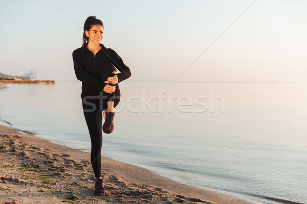 Healthy young sportswoman doing stretching exercises Stock photo © deandrobot