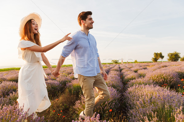 Photo of joyful young couple man and woman dating, and walking o Stock photo © deandrobot