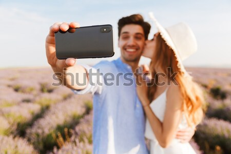 Photo of joyous young man and woman taking selfie, while walking Stock photo © deandrobot