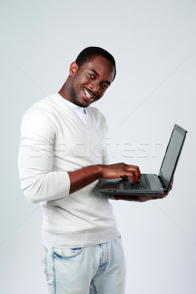 African man working on laptop while standing up on gray background Stock photo © deandrobot