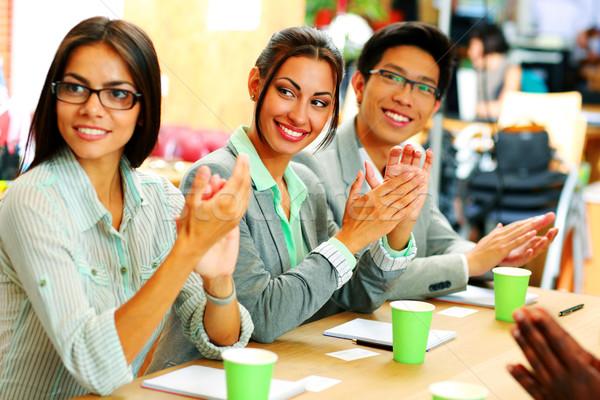 Stock photo: Cheerful business people applauding in a meeting. Business concept.
