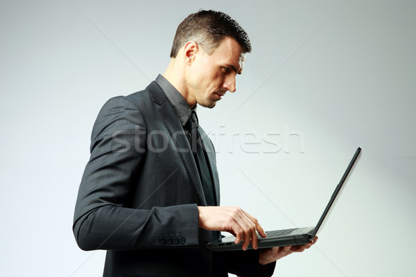 Confident businessman using laptop on gray background Stock photo © deandrobot