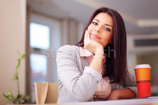 Young confident smiling woman sitting at the table Stock photo © deandrobot